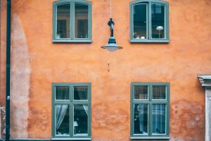 facade house wall orange color with green windows
