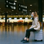 woman wearing a covid mask, sitting on a suitcase in an airport