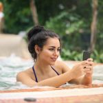 woman in a swimming pool with a phone in her hand