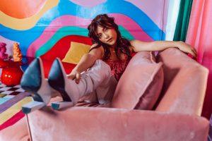 Transgender woman sitting on sofa, colorful room
